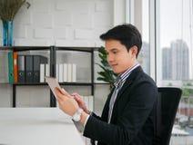 Il giovane uomo asiatico esecutivo si siede e sorride sulla sedia e sulla tenuta fotografia stock