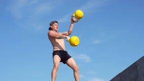 Il giovane uomo atletico che fa la gorilla di esercizio pesa all'aperto Crossfit Movimento lento video d archivio
