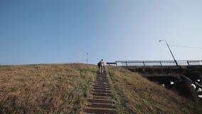 Il giovane uomo attivo con lo zaino scala le scale sul ponte sotto la montagna dell'erba stock footage
