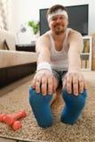 Il giovane uomo attraente di forma fisica si trova su una stuoia grassa con Immagine Stock Libera da Diritti