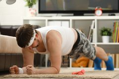 Il giovane uomo attraente di forma fisica si trova su una stuoia grassa con Immagine Stock