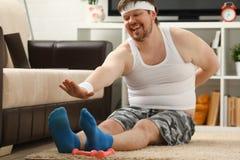 Il giovane uomo attraente di forma fisica si trova su una stuoia grassa con Fotografie Stock