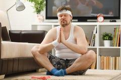 Il giovane uomo attraente di forma fisica si trova su una stuoia grassa con Immagini Stock Libere da Diritti