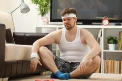 Il giovane uomo attraente di forma fisica si trova su una stuoia grassa con Fotografia Stock
