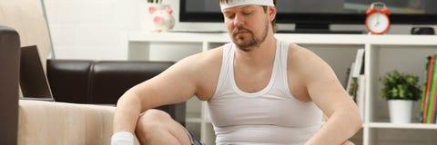 Il giovane uomo attraente di forma fisica si trova su una stuoia grassa con Fotografie Stock Libere da Diritti