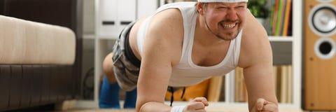 Il giovane uomo attraente di forma fisica si trova su una stuoia grassa con Fotografia Stock Libera da Diritti