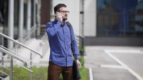 Il giovane uomo barbuto bello in camicia blu e pantaloni marroni sta stando all'aperto e sta parlando sul telefono Uomo d'affari video d archivio