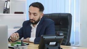 Il giovane uomo barbuto bello utilizza la compressa dello schermo attivabile al tatto nell'ufficio startup moderno video d archivio