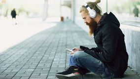 Il giovane uomo barbuto dei pantaloni a vita bassa con le cuffie che si siedono sulla strada e che per mezzo dello smartphone per immagini stock