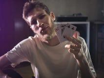 Il giovane uomo barbuto nelle carte casuali del playng della tenuta mostra il ritratto di alcuni trucchi a casa fotografie stock