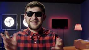 Il giovane uomo barbuto parla ed attivamente applaude in studio ammobiliato moderno scuro stock footage