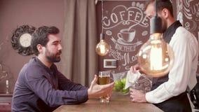 Il giovane uomo barbuto racconta una storia al barista ed alla birra delle bevande video d archivio
