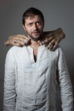 Il giovane uomo barbuto si è soffocato da due mani enormi Immagini Stock