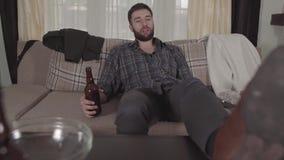 Il giovane uomo barbuto si siede sul sof? con la bottiglia di birra a disposizione e la bevanda, quindi mette i piedi sulla tavol video d archivio