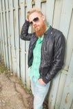 Il giovane uomo barbuto sistema i suoi capelli Fotografia Stock Libera da Diritti