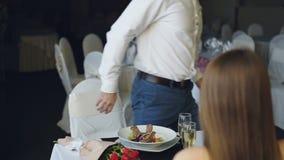 Il giovane uomo barbuto sta discutendo con la sua amica mentre pranzava nel ristorante poi che va Litigio degli amanti, negativo stock footage