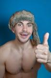 Il giovane uomo bello allegro in cappello di pelliccia alla moda dei pantaloni a vita bassa con le emozioni pazze acconsente e so Fotografia Stock Libera da Diritti