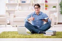 Il giovane uomo bello che si siede sul pavimento a casa Immagini Stock