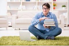 Il giovane uomo bello che si siede sul pavimento a casa Fotografia Stock