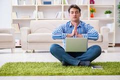 Il giovane uomo bello che si siede sul pavimento a casa Fotografie Stock