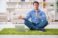 Il giovane uomo bello che si siede sul pavimento a casa Immagini Stock Libere da Diritti