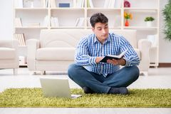 Il giovane uomo bello che si siede sul pavimento a casa Fotografia Stock Libera da Diritti