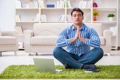 Il giovane uomo bello che si siede sul pavimento a casa Immagine Stock