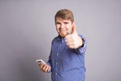Il giovane uomo bello che tiene il suo smartphone e che mostra il gesto sfoglia su Immagini Stock Libere da Diritti