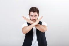 Il giovane uomo bello con la barba in camicia bianca e panciotto nero mostra la fermata di gesto Immagine Stock