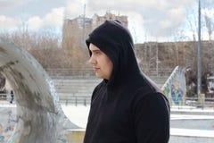Il giovane uomo bello in maglia con cappuccio nera sta sulla via Immagine Stock Libera da Diritti
