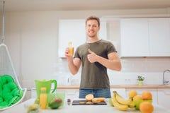 Il giovane uomo bello tiene il pollice su ed il succo d'arancia mentre taglia la frutta fresca nella cucina Alimento sano vegetar immagini stock libere da diritti