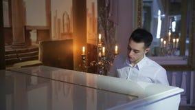 Il giovane uomo castana sveglio del primo piano in camicia bianca gioca il pianoforte a coda bianco video d archivio