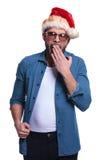 Il giovane uomo casuale in cappello di Santa sta sbadigliando Fotografia Stock Libera da Diritti
