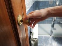 Il giovane uomo caucasico apre la porta del bagno Mano su door& x27; fine della maniglia di s su Doccia con le mattonelle blu nel fotografie stock