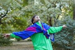 Il giovane uomo caucasico bello con stile pazzo luminoso degli abiti sportivi 70s sta ad un parco di mattina Bastone nella bocca, fotografie stock