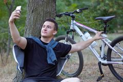 Il giovane uomo caucasico bello fa il selfie sul telefono cellulare, sedentesi sulla terra vicino al grande albero al parco abban immagine stock