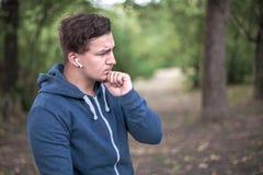 Il giovane uomo caucasico tocca il suo mento thoughful fotografie stock