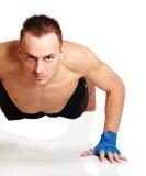 Il giovane uomo che di forma fisica fare spinge aumenta sul pavimento fotografie stock
