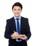 Il giovane uomo d'affari asiatico scrive sulla lavagna per appunti Immagini Stock
