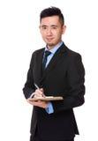 Il giovane uomo d'affari asiatico scrive sulla lavagna per appunti Immagini Stock Libere da Diritti