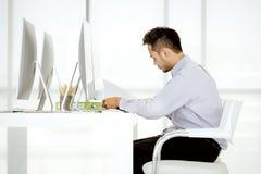 Il giovane uomo d'affari asiatico in un casuale sta sedendosi il concentrato e la i fotografie stock libere da diritti