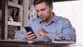 Il giovane uomo d'affari barbuto attraente in una camicia blu utilizza uno smartphone Resto da lavoro Gestore soddisfatto stock footage