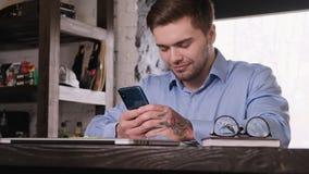 Il giovane uomo d'affari barbuto attraente in una camicia blu utilizza uno smartphone Resto da lavoro Gestore soddisfatto video d archivio