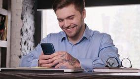 Il giovane uomo d'affari barbuto attraente in una camicia blu utilizza uno smartphone Resto da lavoro Gestore soddisfatto archivi video