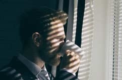 Il giovane uomo d'affari barbuto bello sta guardando fuori la finestra Fotografia Stock