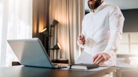 Il giovane uomo d'affari barbuto in camicia bianca è scrittorio vicino diritto davanti al computer portatile, documenti della ten immagine stock libera da diritti