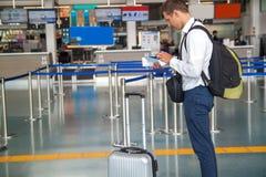 Il giovane uomo d'affari bello in camicia bianca che allunga fuori il suo biglietto mentre sta davanti alla linea aerea controlla fotografia stock libera da diritti