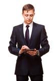 Il giovane uomo d'affari bello sta lavorando alla sua compressa digitale isolata su fondo bianco Fotografia Stock