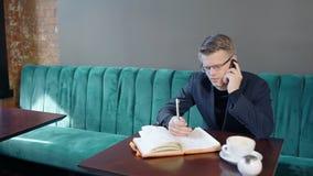 Il giovane uomo d'affari bello sta parlando sul telefono, sedentesi alla tavola in caffè stock footage