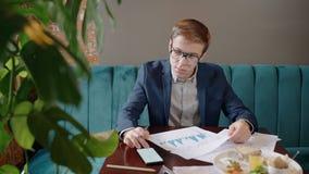 Il giovane uomo d'affari bello sta utilizzando lo smartphone, funzionante con i documenti archivi video